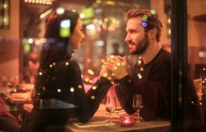 man and woman holding hands at restaurant with 2 wine glasses